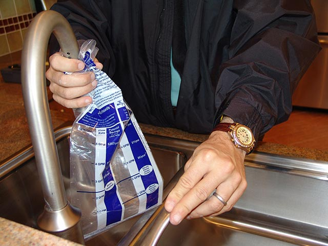 Man filling bag of water audit kit