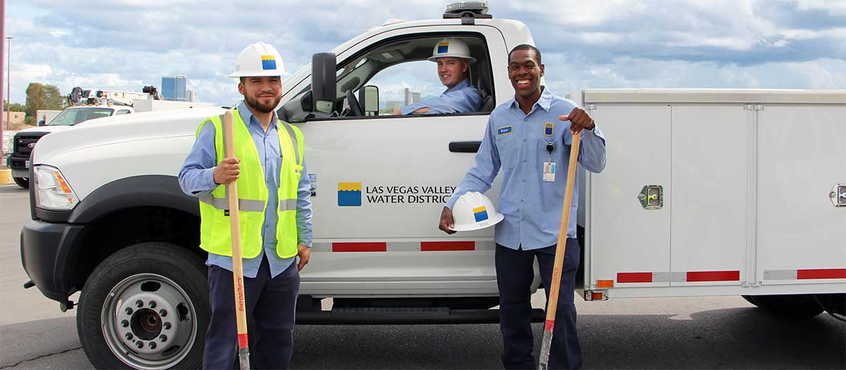 las vegas valley water district employees stand next to a work truck