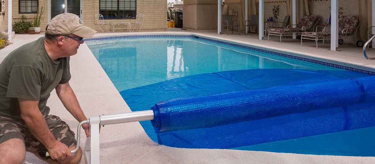 Man covering pool with tarp