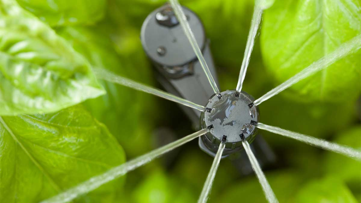 sprinkler irrigation head closeup against green leaf background